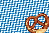 german oktoberfest pretzel on checkered pattern background
