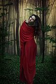 Beautiful woman in red in forest