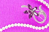 Brooch and pearl necklace on purple background