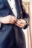 Elegant young business man in tuxedo buttoning the jacket