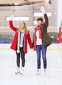 happy girls friends waving hands on skating rink