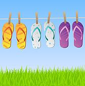 Image of a colorful scene with flip flops hanging on a clothes line with sky and grass.