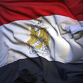 Flag of Egypt, fluttering in the breeze, backlit rising sun