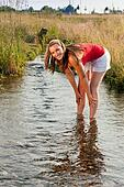 Woman standing in creek summer