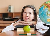 Schoolgirl's portrait at school desk with her books and globe