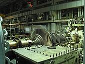 Power generator steam turbine during repair, machinery, pipes, tubes at a power plant, night scene