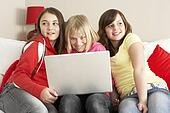 Group Of Three Girls Using Laptop At Home