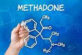 Hand with pen drawing the chemical formula of methadone