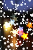 Snow falling over blurred holiday background with star-shaped highlights.