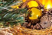 Christmas composition with basket with pine cones and gold Chris