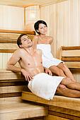 Half-naked man and young woman relaxing in sauna