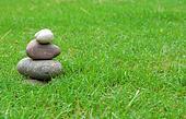 Balance zen stones on green grass