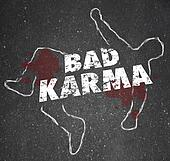 Bad Karma words on a chalk outline of a dead or murdered body to illustrate someone who has wronged others in life and received a similar treatment, destiny or fate as a result