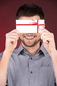 Present gift in hands of smiling man. closeup on happy man standing on red background