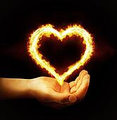 Hand holding fire heart on black background