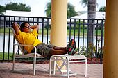 Hispanic man relaxing by the pool