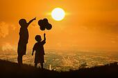 silhouette of asian little boy point to the sun at sunset background