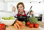 young happy and attractive home cook woman in red apron at domestic kitchen holding saucepan tasting hot soup