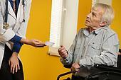 Nurse woman giving client card to senior man in wheelchair