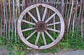 Single old wagon wheel near the wooden fence