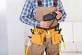 Man Wearing Tool Belt At Home