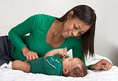 ethnic mother playing with her baby boy son on bed