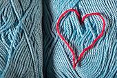 Knitted red heart on blue