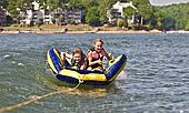 Children Tubing Behind a Boat