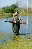 hunter with rifle gun in bog