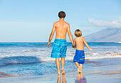 Happy father and son walking together at beach