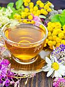Tea from wild flowers in glass cup on board