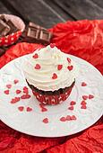 Chocolate cupcake decorated with red hearts