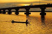 Silhouette of man paddling boat at sunset