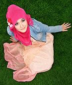 Muslim girl wearing hijab sitting on grass