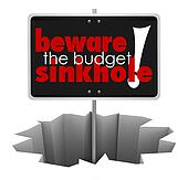 Beware the Budget Sinkhole Sign Hole Money Trouble Bankruptcy