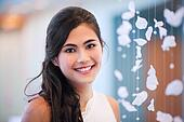 Beautiful biracial bride smiling next to curtain of white rose p