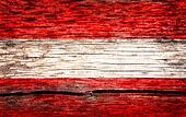 Austria flag painted on the old cracked wood with worn-out paint. Grunge look.