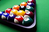 Billiard balls, cue on green table