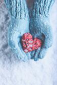 Woman hands in light teal knitted mittens are holding beautiful a entwined vintage red heart on snow. Love, St. Valentine concept