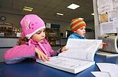 Little boy in striped cap and girl in pink outerwear reading a book carefully inside post office