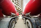 Between two concrete mixer standing near unfinished tall high-rise buildings