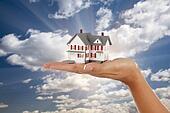 Model House in Female Hand on Sky Background
