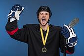 Hockey player is celebrating his victory with happy emotion. Isolated on blue