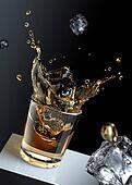 Ice cube splashing into a glas of liquid.