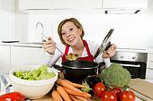 young happy home cook woman in red apron at domestic kitchen holding saucepan tasting hot soup