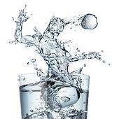 Glass of water with a splash shaped as a soccer player jumping and hitting the ball with his head. Close up view on white background. Concept image.