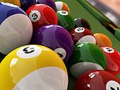 Group of billiard balls with numbers, on green pool table, with a hole in the background. Close up view.