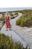 girl is standing on a way to ocean