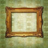 Empty golden frame on Victorian floral green-gold wallpaper