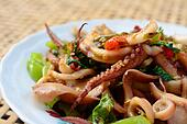 stir-fried squid and basil on white plate and blur bamboo baske